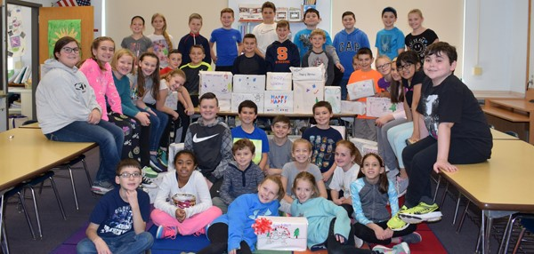 Tioga Hills Elementary fifth-graders pose with the 41 boxes of personal care items they filled, wrapped and decorated for patrons of the Apalachin Food Pantry.