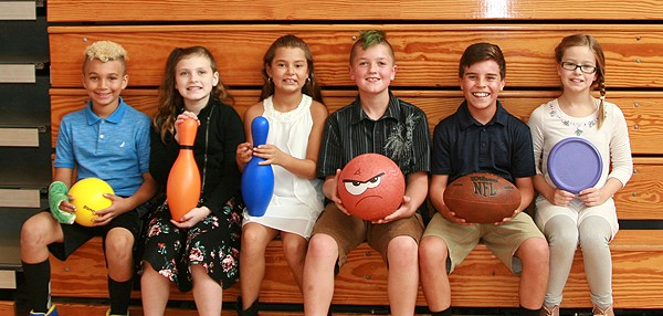 Six students sit on the bleachers in gym class, holding various physical education class equipment such as a football, basketball, frisbee and plastic bowling pins.