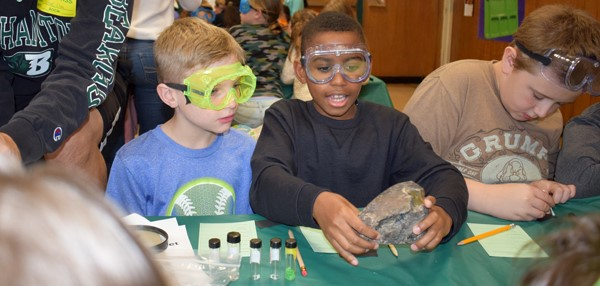 Two boys wearing eye-protecting goggles examine a large mineral specimen during Chemistry Outreach stations coordinated by Binghamton University's Chemistry Club.