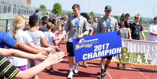 Two Golden Bear baseball teammates high-five Clayton Avenue fans as they carry a N Y S P H S A A  2017 Champion sign around Hoover Stadium