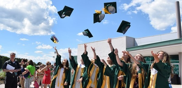 Seven Vestal High School graduates toss their caps into the air outside of the Binghamton University Events Center after Vestal's 2017 commencement ceremony