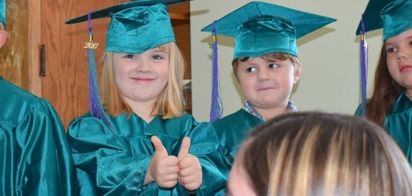 "Girl and boy in green graduation cap & gown wait for their Universal Pre-K graduation ceremony to begin. (Girl making ""thumbs-up"" gesture."