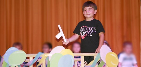 "Small boy crosses a bridge decorated with pink, yellow and blue paper balloons as he clutches his Universal Pre-K ""graduation"" certificate."