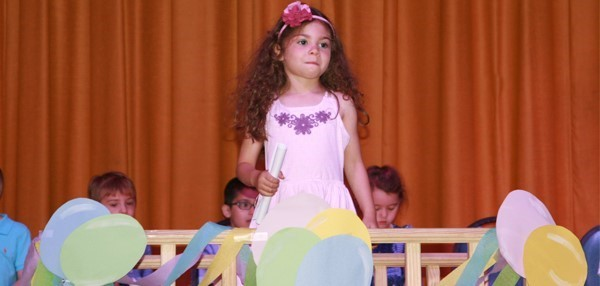 "A small girl in pink dress with long, curly black hair crosses over the bridge during her Universal Pre-K ""graduation"" at the J C C  campus."