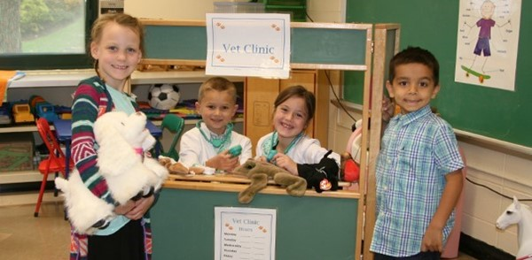 Three kindergarten students play at the vet clinic in the Glenwood Elementary School playroom.