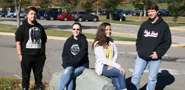 Four Vestal Middle School students socialize outside (sitting on some rocks by the auditorium entrance).