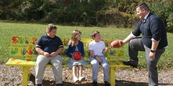 Students sit on the Buddy Bench on the Tioga Hills Elementary School playground as a teacher aide chats with them.
