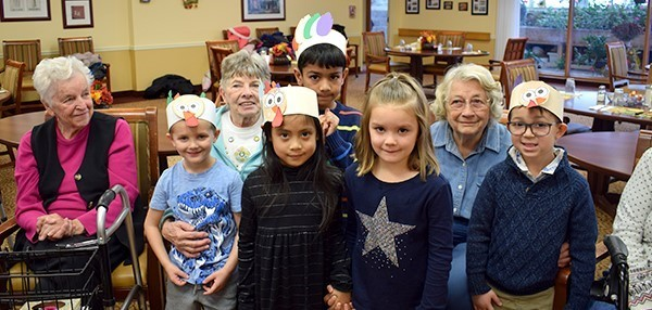Four Kindergarten students from Vestal Hills Elementary in paper turkey hats pose for a group photo with Brookdale residents on November 20, 2018
