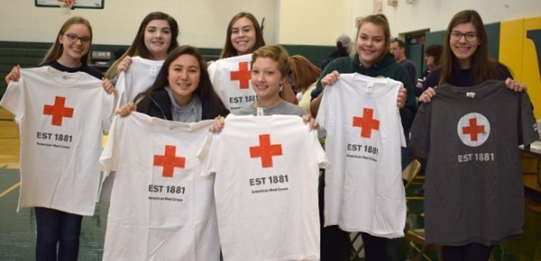 Seven Vestal High School girls hold up the American Red Cross tee-shirts they received after giving blood during the school's Fall Blood Drive in the gym on November 29, 2018