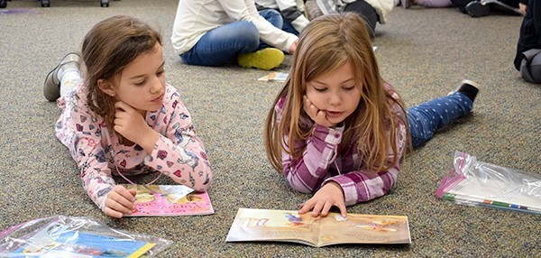 Two first-grade girls from Glenwood lie on  their bellies as one reads a book to the other during their Super Secret field trip to the Super Secret Detective Agency on November 19, 2018
