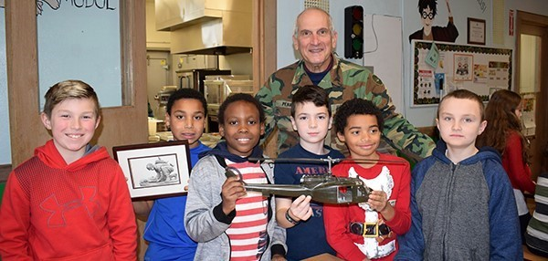 A group of Clayton Avenue fourth-graders hold a model Army helicopter and a framed certificate as they pose for a photo with Army Medical Corps Lt Colonel Penna, retired, in the cafeteria during a reception in honor of Veterans Day