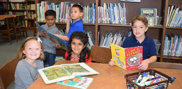 First-graders pick out books to read in the African Road Elementary School library.
