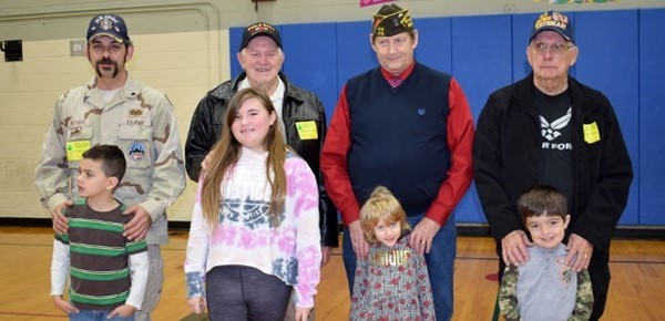 Vestal Hills Elementary students stand in front of their fathers, grandfathers and great grandfathers who are veterans after the Veterans Day ceremony on November 8 in the gym