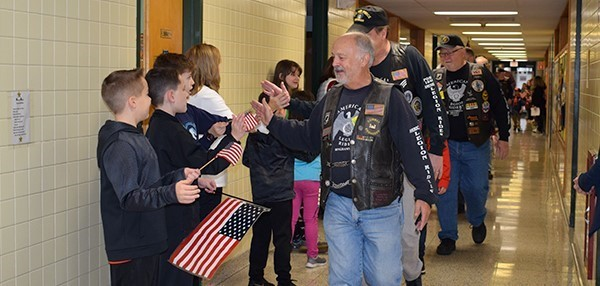 Tioga Hills Elementary students lining the hallways clap and wave flags as local veterans pass them in a parade prior to the Veterans Day ceremony on November 9, 2018