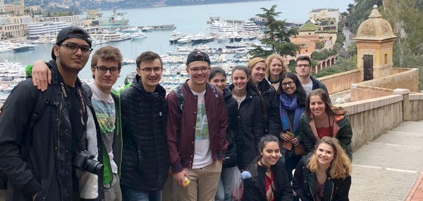 A group of Vestal High School French Club students visiting France are shown with a beautiful harbor with boats in the background.