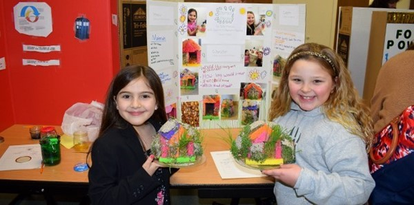 Two African Road Elementary students hold their second-grade science project, Sprout Houses, in front of the display board on their experiment during the student preview of the Science Fair on March 8, 2018.