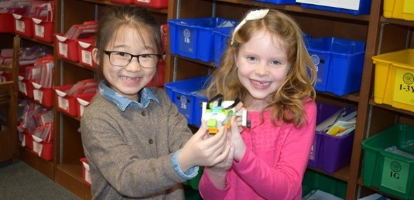 Two second-graders in the African Road Elementary School library proudly hold the WeDo 2.0 Tadpole robot they built and programmed, which just won a race against classmates' robots.