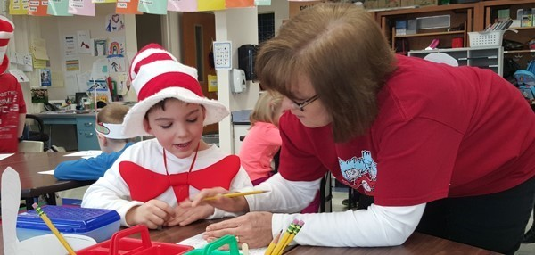 "An aide helps a boy with a math exercise that is part of the Dr. Seuss fun in his first-grade classroom on March 5, 2018. He is wearing a cloth, red-and-white striped ""Cat in the Hat-"" style hat."