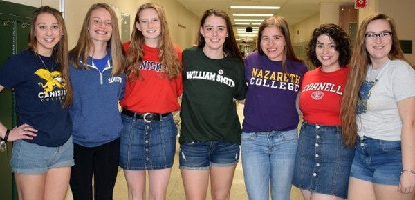 A group of Vestal High School girls pose in the hallway of the Vestal High School wearing shirts from the colleges they will be attending in the Fall