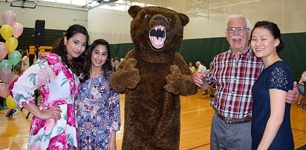 Three Vestal High School seniors and the Vestal Golden Bear mascot pose for a photo with one of their Swing into Spring Dance guests in the school gym on May 18, 2018