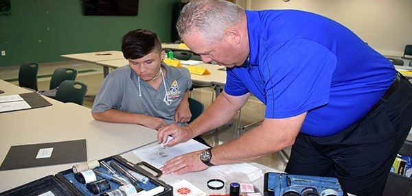 Lt. Streno of the Vestal Police Department shows a cadet how he would collect fingerprint evidence at the end of his Criminal Scene Investigation presentation during the Youth Police Academy on July 10, 2018