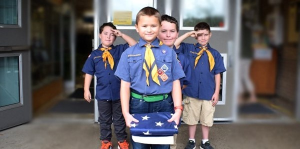 Members of Cub Scout Troop 243 wait at the entrance of Glenwood Elementary School on September 11, 2018, with a folded American flag as they prepare to begin the school's Patriot Day ceremony