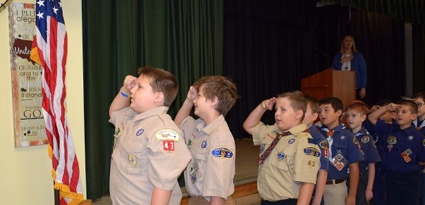 Webelos Scouts put fingers to forehead in the Cub Scout salute as they face the flag in the Tioga HIlls Elementary School cafeteria for Patriot Day on September 11, 2018