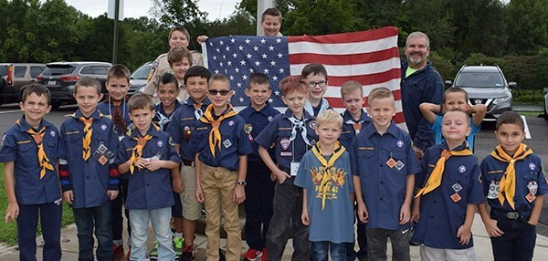 Scouts of the Pack 43 surround the flag prior to raising it to half-mast during Tioga Hills Elementary School's Patriot Day ceremony on September 11, 2018