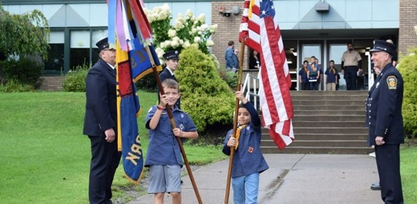 Two boys carry an American flag and a Cub Scout flag as they participate in Glenwood Elementary School's Patriot Day ceremony on September 11, 2018
