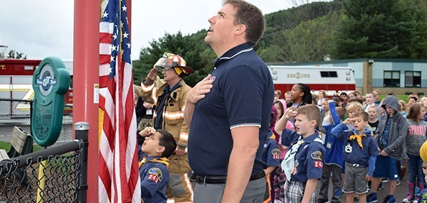 Cub Scouts and Vestal Fire personnel salute the flag along with the Glenwood Elementary School student body as the flag is raised to half mast on the flagpole in the school's playground on September 11, 2018