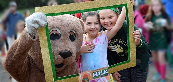 Holding a cardboard picture frame, two girls pose for a photo with the Vestal Golden Bear outside African Road Elementary School during the Walk-to-School Day celebration in October 2018.