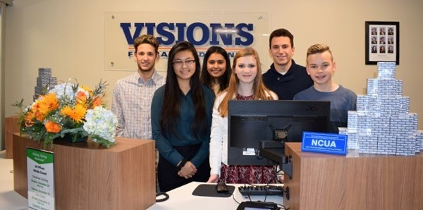 Vestal High School students hired to staff the new Visions Federal Credit Union branch in their school lobby pose inside the new facility after the ribbon-cutting ceremony in November 2018