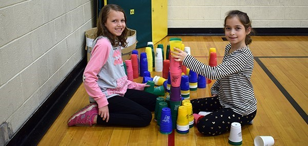 Taking part in the World Cup Stacking Challenge, two Vestal Hills Elementary School girls stack cups during gym class in November.