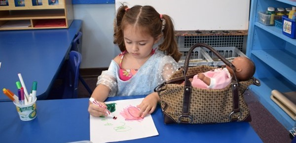 Dressed in a blue princess dress, a new Universal Pre-Kindergarten girl carefully colors an artistic masterpiece she is working on during the student orientation in August 2018.